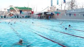 Moskva Ryssland, Februari 16, 2019: Det aktiva folket simmar utomhus- i en sportpöl Chayka i vinter Simma i det öppet lager videofilmer