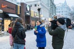 Moskva Ryssland - Februari 11, 2018 Korrespondent av intervjun för TV- och radioföretagsMir-tagande med förbipasserande på gamla  royaltyfria bilder