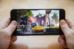 Moskva/Ryssland - Februari 24, 2019: ladda pubg spela på en svart smartphone i manliga händer arkivbild