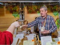 Moskva Ryssland - Februari 25, 2017: Representanten på de ganska erbjudandena som ska försökas hem, producerade honung från hans  royaltyfria bilder