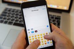 Moskva/Ryssland - Februari 20, 2019: skriva ett nytt meddelande på iPhonen på bakgrunden av MacBook arkivbild