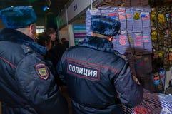 Moskva Ryssland - Februari 25, 2017: Två rysspoliser som besöker ställningen med roliga militär-patriotiska t-skjortor Royaltyfri Fotografi