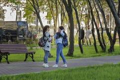 MOSKVA RYSSLAND - 2017-05-14: Flickor som har ett livligt samtal i Krigare-vinnarna, parkerar i den Lefortovo grannskapen arkivbild