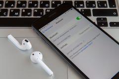 Moskva Ryssland - Januari 29, 2019 IPhone och airpodshörlurar ligger på macbooktangentbordet Bluetooth är på royaltyfri foto