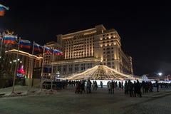 MOSKVA RYSSLAND - Januari 10 2016 Nattsikt av folk som går på den Manezh fyrkanten och hotellet fyra säsonger Arkivfoton