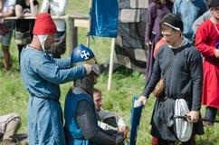 MOSKVA Ryssland-Juni 06,2016: Den medeltida krigaren förbereder sig för duell Följet av riddaren klär hjälmen för duell Arkivbild