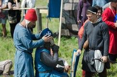 MOSKVA Ryssland-Juni 06,2016: Den medeltida krigaren förbereder sig för duell Följet av riddaren klär hjälmen för duell Arkivbilder