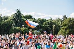 MOSKVA RYSSLAND - JUNI 2018: En fotbollsfan vinkar en rysk nationsflagga i en folkmassa i fanzonen under världscupen arkivbilder