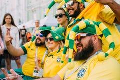 MOSKVA RYSSLAND - JUNI 2018: En grupp av brasilianska fotbollsfan fotograferas med ryska flickor på gatan under royaltyfri foto