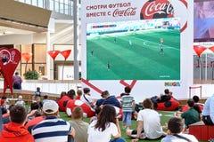 Moskva Ryssland - Juni 16,2018 Folk som håller ögonen på en Fifa-världscupradioutsändning på den stora skärmen i köpcentrum Arkivfoto
