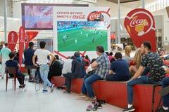 Moskva Ryssland - Juni 16,2018 Folk som håller ögonen på en Fifa-världscupradioutsändning på den stora skärmen i köpcentrum Royaltyfri Bild