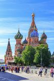 Moskva Ryssland - Juni 03, 2018: Gå turister på röd fyrkant nära domkyrka för St-basilika` s på en solig sommarmorgon Royaltyfri Bild