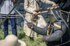 MOSKVA Ryssland-Juni 06,2016: Krigs- duell av två medeltida teutonic krigare Oavkortad pansarkamp för riddare med svärd på arenan Royaltyfri Fotografi