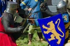 MOSKVA Ryssland-Juni 06,2016: Medeltida krigarekamp på duell Riddare kämpar i pansar med svärd och sköldar i där händer Royaltyfri Fotografi