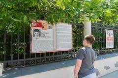 Moskva Ryssland - Juni 02 2016 Tonårig pojke som läser ett fragment av barns bok av kriget på den Myasnitskaya gatan Royaltyfri Fotografi