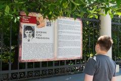 Moskva Ryssland - Juni 02 2016 Tonårig pojke som läser ett fragment av barns bok av kriget på den Myasnitskaya gatan Fotografering för Bildbyråer