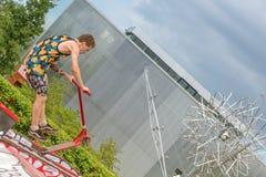 Moskva Ryssland - Juni 21, 2018: Ung man med hoppa för sparkcykel arkivbilder