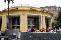 Moskva Ryssland, kan 25, 2019: rund gul byggnad av den Novokuznetsk tunnelbanastationen i f?rgrundsblomsterrabatterna med ljust royaltyfria foton