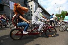 MOSKVA RYSSLAND - 20 Maj 2002: Att cykla för stad ståtar, hästen, och dalmationen kostymerade deltagare på en tandem cykel arkivfoton