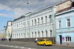Moskva Ryssland, Maj, 19, 2017 Gul bil av taxien på den Spartakovskaya gatan nära huset nummer 10/2 Bostads- byggnad är dat Royaltyfri Fotografi