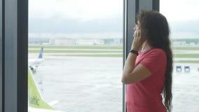 MOSKVA RYSSLAND - MAJ 25, 2017 Kvinna som talar på telefonen på flygplatsen nära fönstret arkivfilmer