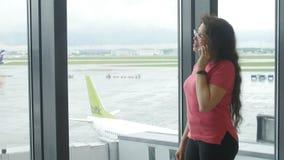 MOSKVA RYSSLAND - MAJ 25, 2017 Kvinna som talar på telefonen på flygplatsen nära fönstret lager videofilmer