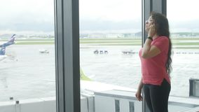 MOSKVA RYSSLAND - MAJ 25, 2017 Kvinna som talar på telefonen på flygplatsen nära fönstret stock video