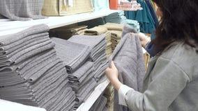 MOSKVA RYSSLAND, MAJ 20, 2016: Kvinna som väljer Grey Terry Towel In Department Store stock video