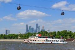 Moskva Ryssland - Maj 30, 2018: Nöjefartyg som svävar på en bakgrund av Luzhniki stadion med ropewayen över den Moskva floden in royaltyfria bilder