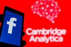 MOSKVA RYSSLAND - MAJ 9, 2018: Smartphone i hand med logo av det populära sociala nätverket Facebook Cambridge Analytica emblem arkivbilder