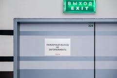 MOSKVA RYSSLAND - MARS 28, 2018: Brandutgång i en stor köpcentrumTROJKA Plakat med utgången för text`-brand Blockera inte `, royaltyfri foto