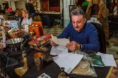 Moskva Ryssland - mars 19, 2017: En äldre gråhårig man i pensionsålder läser dokumentet med handskriven text Arkivbilder