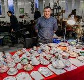Moskva Ryssland - mars 19, 2017: Kontra med antika porslinware på loppmarknaden Selektiv fokus på disken Royaltyfri Fotografi