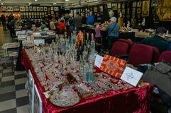 Moskva Ryssland - mars 19, 2017: Tabell på loppmarknaden med antika flaskor av olika format och färger Royaltyfri Fotografi