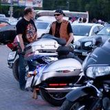 MOSKVA RYSSLAND - OKTOBER 6, 2013: Cyklisten i en bandana talar med andra män Arkivfoton