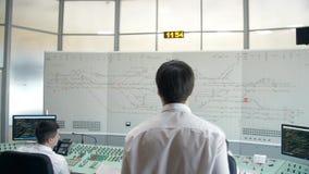 MOSKVA RYSSLAND - VÅR: Dispatcher av järnvägen på arbete Drevschemabildskärmar, drevkontrollbord lager videofilmer