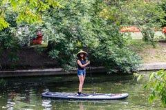 Moskva sommar Parkera-Juli 05, 2018: en ung flicka med en skovel och i en sugrörhatt står på en surfingbräda på ett damm fotografering för bildbyråer