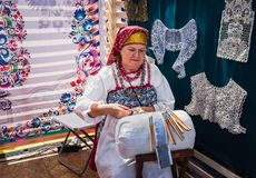 Moskva Victory Park, 11 Juni 2018: En äldre kvinna i den ryska nationella dräkten som kopplas in i traditionellt hantverk arkivbilder