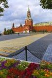 MoskvaKreml, Spasskaya torn, röd fyrkant på ottan som inramas av sidor och blommor Royaltyfria Bilder