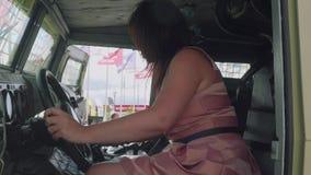 Moskvaregion, Ryssland - Augusti 22, 2018: Kvinnan i rosa klänning är på hjulet av den militära bilen som visar cansole och lager videofilmer