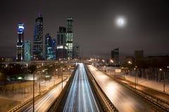 Moskvastadsskyskrapor och huvudväg på fullmånenatten Arkivfoto