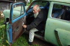 年长人在一辆老苏维埃做的汽车, Moskvich 403坐。 免版税库存图片