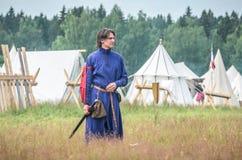MOSKWA, czerwiec 06,2016: Mężczyzna w antycznych wojownika kostiumu stojakach na zieleni polu trawa Zdjęcie Stock