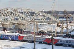 MOSKWA, FEB 01, 2018: Widok na Rosyjskich kolej pociągach pasażerskich biega pod nowym metalu mostem w budowie Zimy industr Fotografia Stock