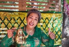 Moskwa, park na Krasnaya Presnya, Sierpień 05, 2018: starsza kobieta od Indonezja w zielonej sukni uśmiecha się herbaty i oferuje zdjęcie royalty free