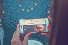 MOSKWA ROSJA, CZERWIEC, - 4, 2019: Alpari pieniężnej firmy strona internetowa na smartphone w kobiet rękach obraz royalty free