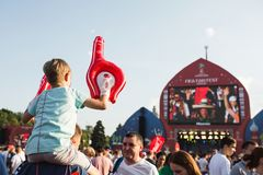 MOSKWA ROSJA, CZERWIEC, - 2018: Chłopiec obsiadanie na jego tata ` s plecy dopatrywania futbolu przy fan festiwalem w Moskwa na V Obraz Royalty Free