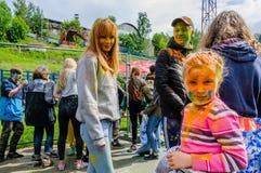 Moskwa Rosja, Czerwiec, - 3, 2017: Mała dziewczynka, plamiąca z pomarańczową farbą na tle inny uczestnika festiwal Holi fotografia stock
