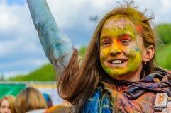 Moskwa Rosja, Czerwiec, - 3, 2017: Mała dziewczynka z radosnym uśmiechem i barwiąca twarz na wakacje letni Holi Fotografia Royalty Free