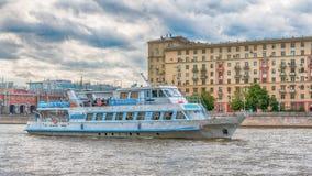 Moskwa Rosja, Czerwiec, - 21, 2018: Przyjemności łódź z turystami unosi się na tle most nad Moskva rzeką na letnim dniu zdjęcia stock